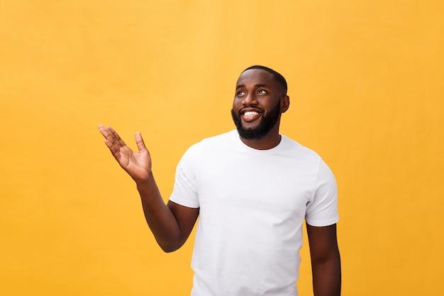 Afrikaanse amerikaanse mens met baard die hand weg kant toont die over gele achtergrond wordt geïsoleerd