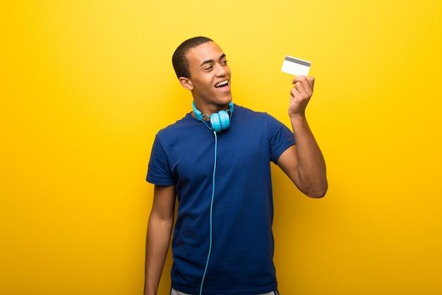 Afrikaanse amerikaanse mens met blauwe t-shirt op gele achtergrond die een creditcard en het denken houden