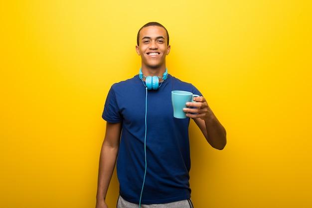 Afrikaanse amerikaanse mens met blauwe t-shirt op gele achtergrond die een hete koffie houdt