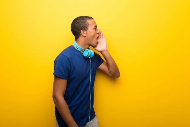 Afrikaanse amerikaanse mens met blauwe t-shirt op gele achtergrond die met mond wijd open aan de zijlijn schreeuwt
