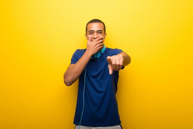 Afrikaanse amerikaanse mens met blauwe t-shirt op gele achtergrond die met vinger richt
