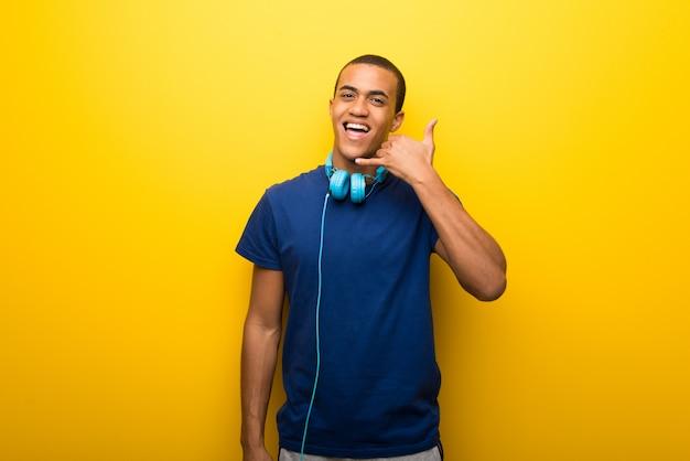 Afrikaanse amerikaanse mens met blauwe t-shirt op gele achtergrond die telefoongebaar maakt