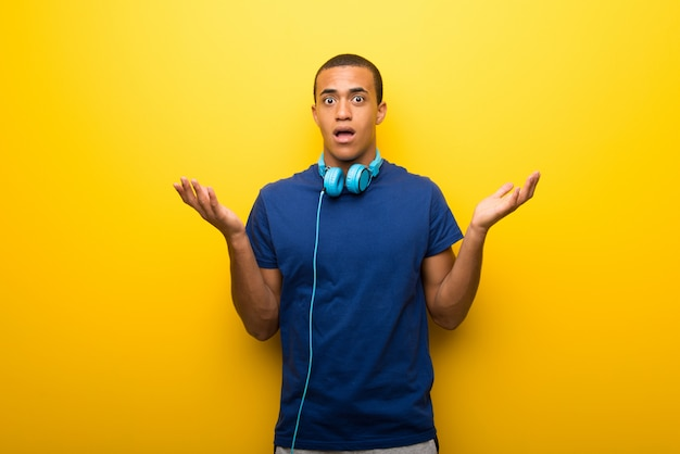 Afrikaanse amerikaanse mens met blauwe t-shirt op gele achtergrond die twijfels hebben