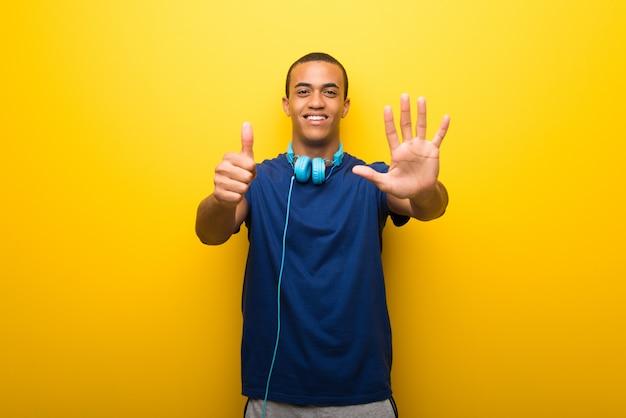 Afrikaanse amerikaanse mens met blauwe t-shirt op gele achtergrond die zes met vingers telt