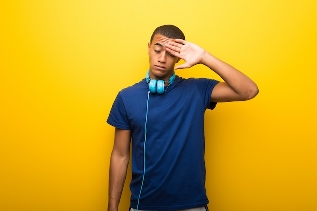 Afrikaanse amerikaanse mens met blauwe t-shirt op gele achtergrond met vermoeide en zieke uitdrukking