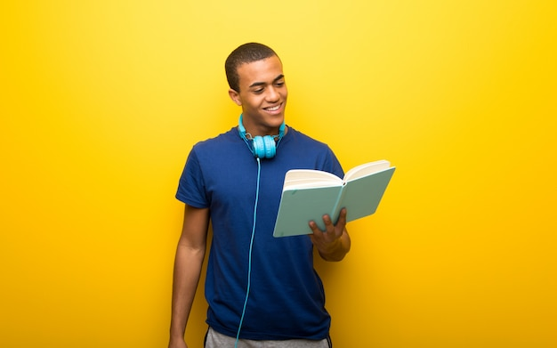 Afrikaanse amerikaanse mens met blauwe t-shirt op gele holding als achtergrond