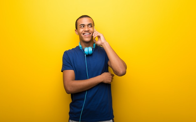 Afrikaanse amerikaanse mens met blauwe t-shirt op gele muur die een gesprek met de mobiele telefoon met iemand houden