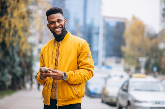Afrikaanse amerikaanse student die in de straat loopt en op de telefoon spreekt