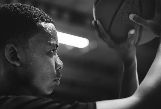 Afrikaanse amerikaanse tiener geconcentreerd op het spelen van basketbal