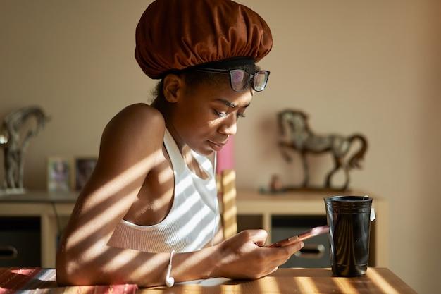 Afrikaanse amerikaanse vrouw die douchemuts draagt en mobiel gebruikt