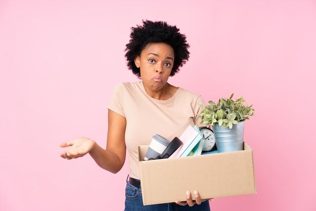Afrikaanse amerikaanse vrouw die een beweging maakt terwijl hij een doos vol dingen oppakt