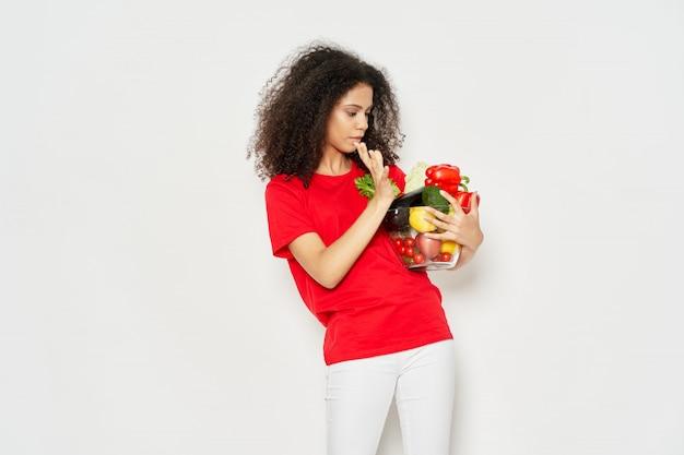 Afrikaanse amerikaanse vrouw die een komhoogtepunt van groenten houdt