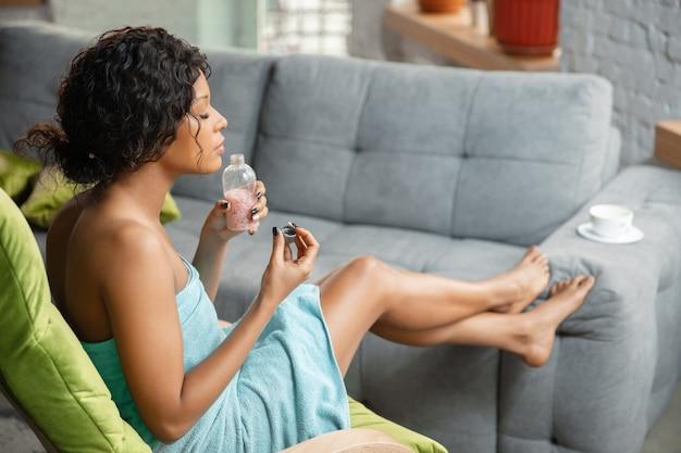 Afrikaanse amerikaanse vrouw die handdoek draagt die haar dagelijkse huidverzorgingsroutine thuis doet.