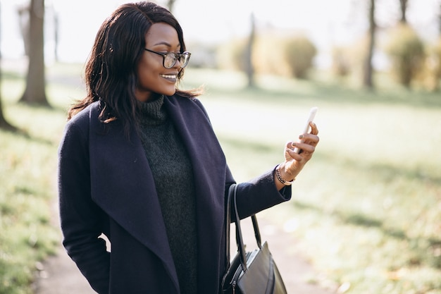 Afrikaanse amerikaanse vrouw die op de telefoon in park spreekt