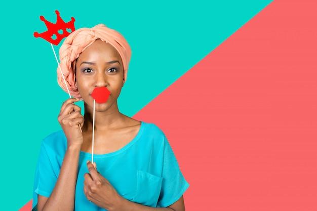 Afrikaanse amerikaanse vrouw die pret met fotosteunen heeft