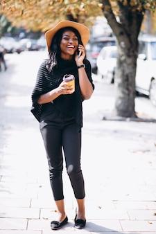 Afrikaanse amerikaanse vrouw koffie drinken en praten aan de telefoon