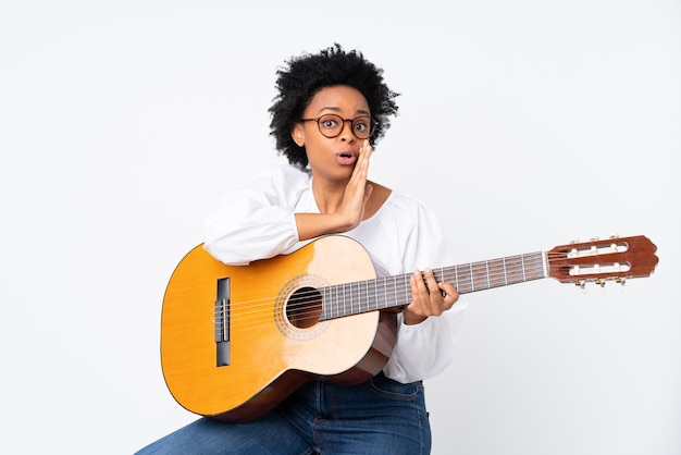 Afrikaanse amerikaanse vrouw met een gitaar over geïsoleerde witte muur