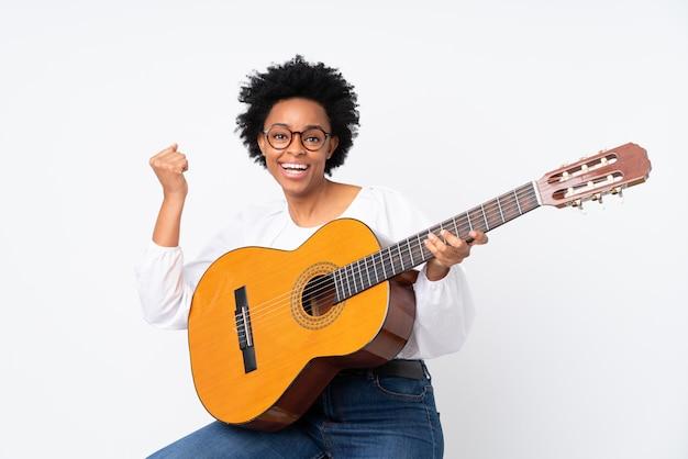 Afrikaanse amerikaanse vrouw met een gitaar over witte muur