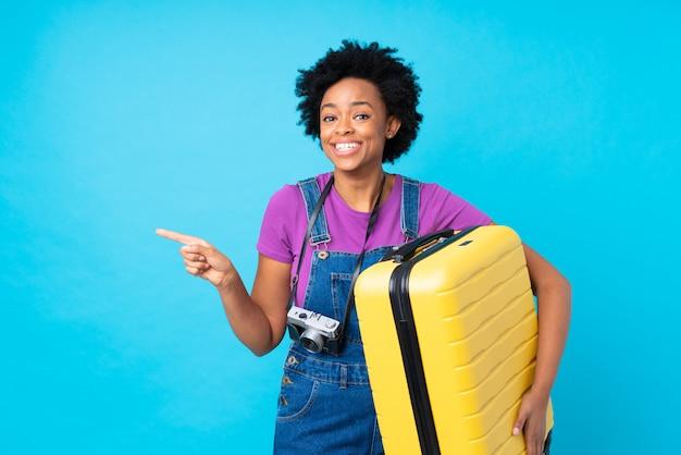 Afrikaanse amerikaanse vrouw met gele koffer over geïsoleerde blauwe muur