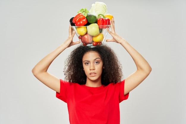 Afrikaanse amerikaanse vrouw met komhoogtepunt van groenten op het hoofd