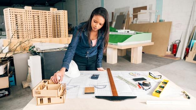 Afrikaanse amerikaanse vrouw met model van huis op lijst dichtbij veiligheidshelm en materiaal