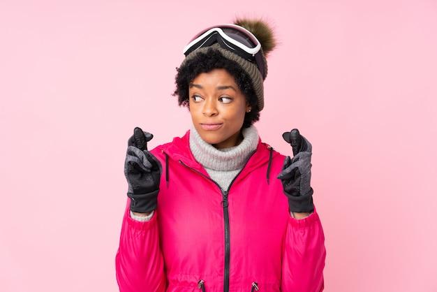 Afrikaanse amerikaanse vrouw met sneeuwbeschermende brillen over roze muur