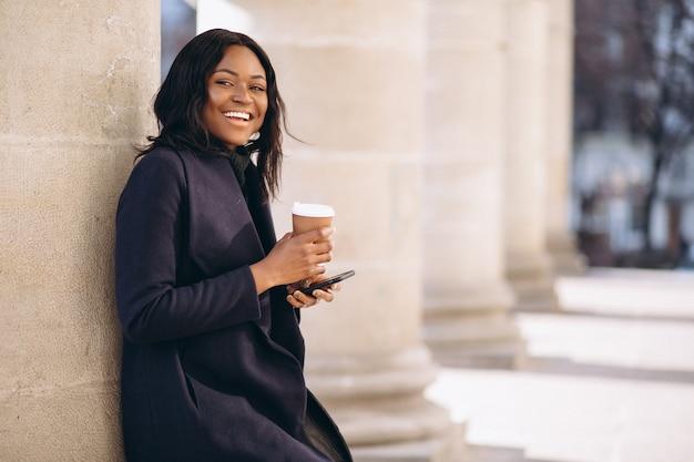 Afrikaanse amerikaanse vrouw met telefoon drinken koffie
