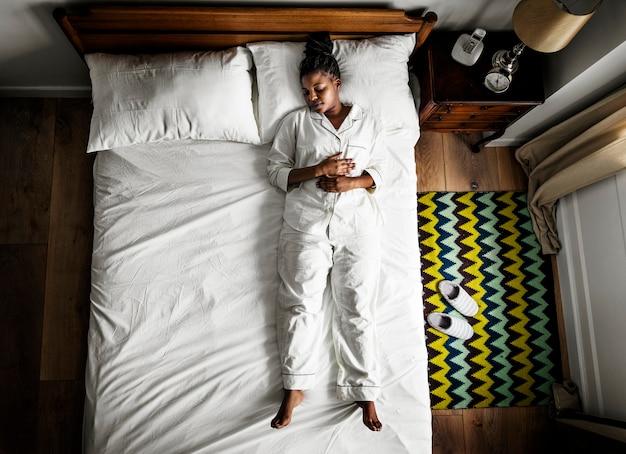 Afrikaanse amerikaanse vrouw op bed die alleen slapen