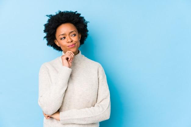 Afrikaanse amerikaanse vrouw van middelbare leeftijd tegen een blauwe muur die zijdelings met twijfelachtige en sceptische uitdrukking kijkt.