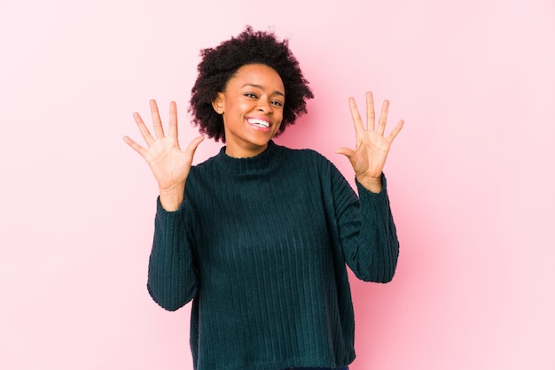 Afrikaanse amerikaanse vrouw van middelbare leeftijd tegen een roze achtergrond die nummer tien met handen toont.