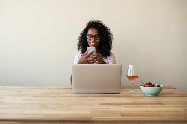 Afrikaanse amerikaanse vrouwelijke freelancer die laptop met behulp van die thuis mobiele telefoon met behulp van