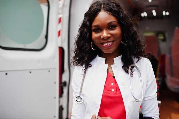 Afrikaanse amerikaanse vrouwelijke paramedicus die zich voor ambulanceauto bevindt