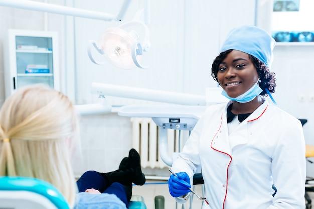 Afrikaanse amerikaanse vrouwelijke tandarts die patiënt behandelen bij kliniek. tandheelkundige kliniek concept.