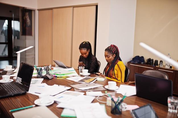 Afrikaanse amerikaanse vrouwencollega's, bemanning van divercity vrouwelijke partners in bureau zitten aan de tafel.