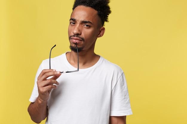Afrikaanse amerikaanse zakenman die een glas houdt, dat op gele achtergrond wordt geïsoleerd
