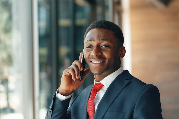 Afrikaanse amerikaanse zakenman die op mobiele telefoon in modern bureau spreekt