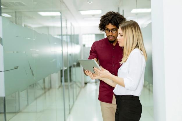 Afrikaanse amerikaanse zakenman en kaukasische onderneemster met de computer die van tabletpc zich in bureau bevinden