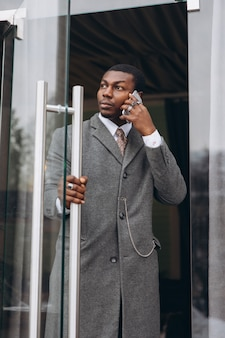 Afrikaanse amerikaanse zakenman in klassiek grijs kostuum terwijl het verlaten van het bureaugebouw