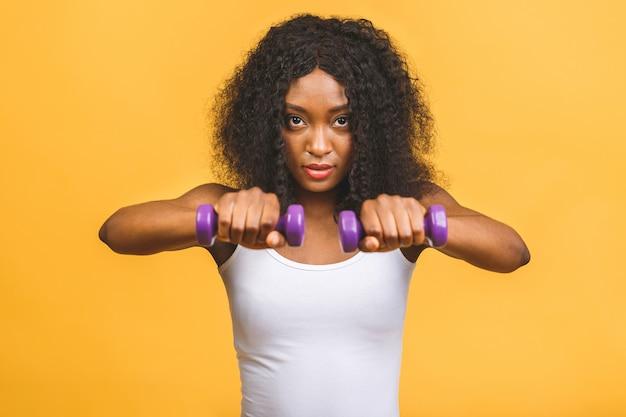 Afrikaanse amerikaanse zwarte jonge vrouw die haar spier met domoren uitoefent