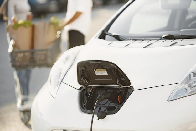 Afrikaanse arabische echtpaar staat met boodschappen in de buurt van elektrische auto. elektrische auto opladen bij het elektrische tankstation