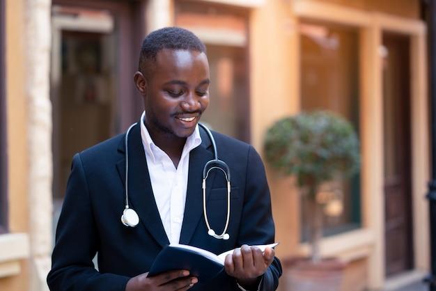 Afrikaanse arts die met stethoscoop klassiek kostuum draagt dat een boek leest dichtbij de moderne bouw van het kliniekziekenhuis