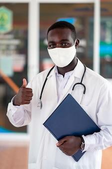 Afrikaanse arts draagt gezichtsmasker en houdt een stethoscoop vast en rapporteert een boek