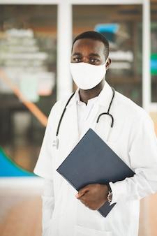 Afrikaanse arts draagt gezichtsmasker met een stethoscoop