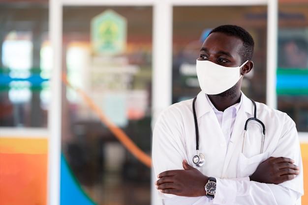 Afrikaanse arts dragen gezichtsmasker en stethoscoop met professioneel en vriendelijk