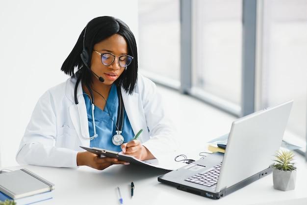 Afrikaanse arts dragen hoofdtelefoon raadplegen vrouwelijke zwarte patiënt online webcam videogesprek op laptop