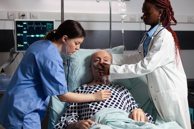 Afrikaanse arts en medisch assistent helpen senior man ademen met behulp van zuurstofmasker, in het ziekenhuis liggend in bed