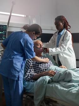 Afrikaanse arts helpt senior patiënt ademen met behulp van beademingsbuis, op de intensive care van de ziekenhuiskamer. oude man opgenomen in het ziekenhuis, gecontroleerd door medisch personeel en behandeld.