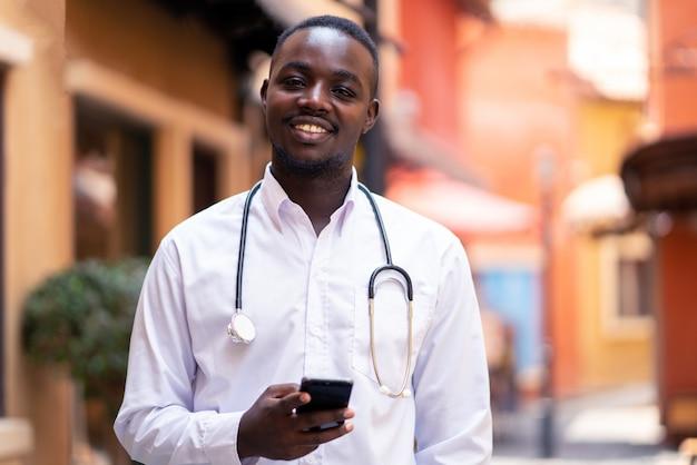Afrikaanse arts met stethoscoop die een smartphone houden dichtbij de moderne bouw van het kliniekziekenhuis