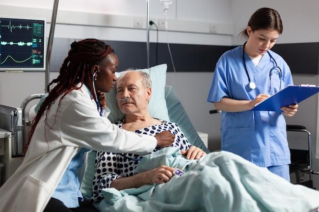 Afrikaanse arts specialist met behulp van stethoscoop luisteren senior man hart