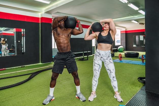 Afrikaanse atleetjongen en blank atleetmeisje in een sportschool die schouderbiceps en borstoefeningen doen met een gewichtsbal in de sportschool. twee multiraciale bodybuilders